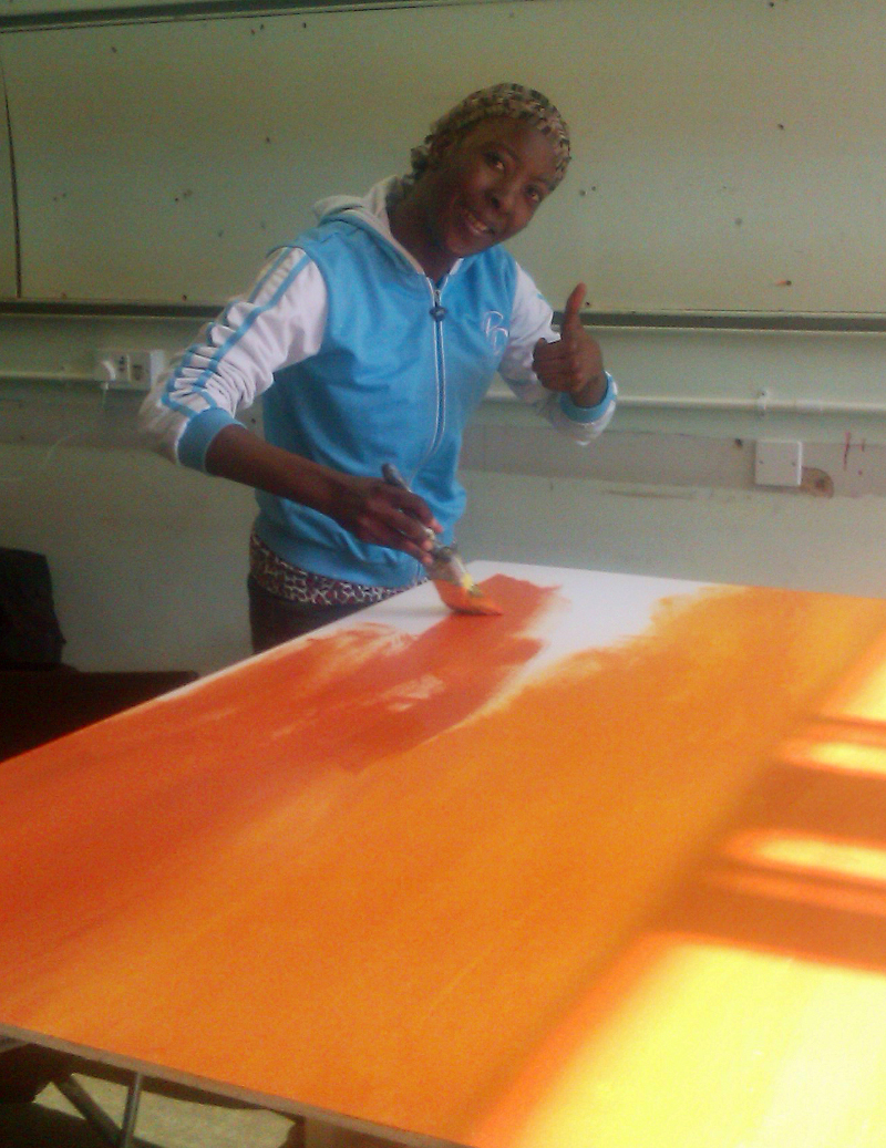 Lucie is looking at the camera and smiling, giving a thumbs-up. She is inside a room and is wearing a blue and white tracksuit top and a headscarf. She is painting the board's background of oranges and yellows.