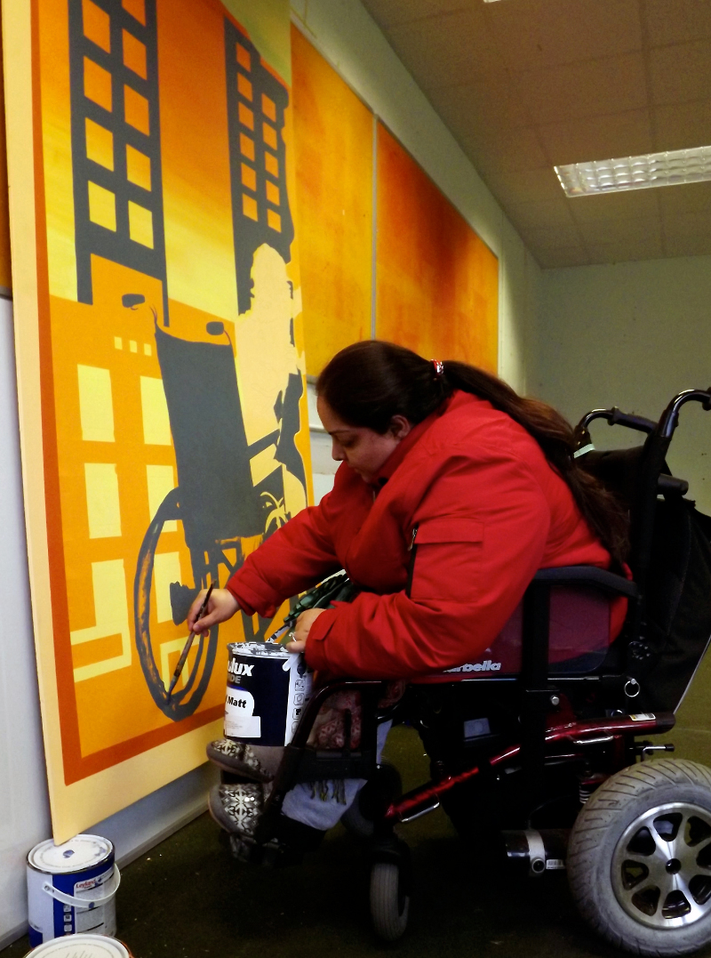 Manjeet is inside painting the mural design onto the boards. Manjeet is a wheelchair user, she is holding a can of paint, painting a blue wheelchair onto an orange background. Manjeet has long dark hair in a pony-tail and she is wearing a red coat.