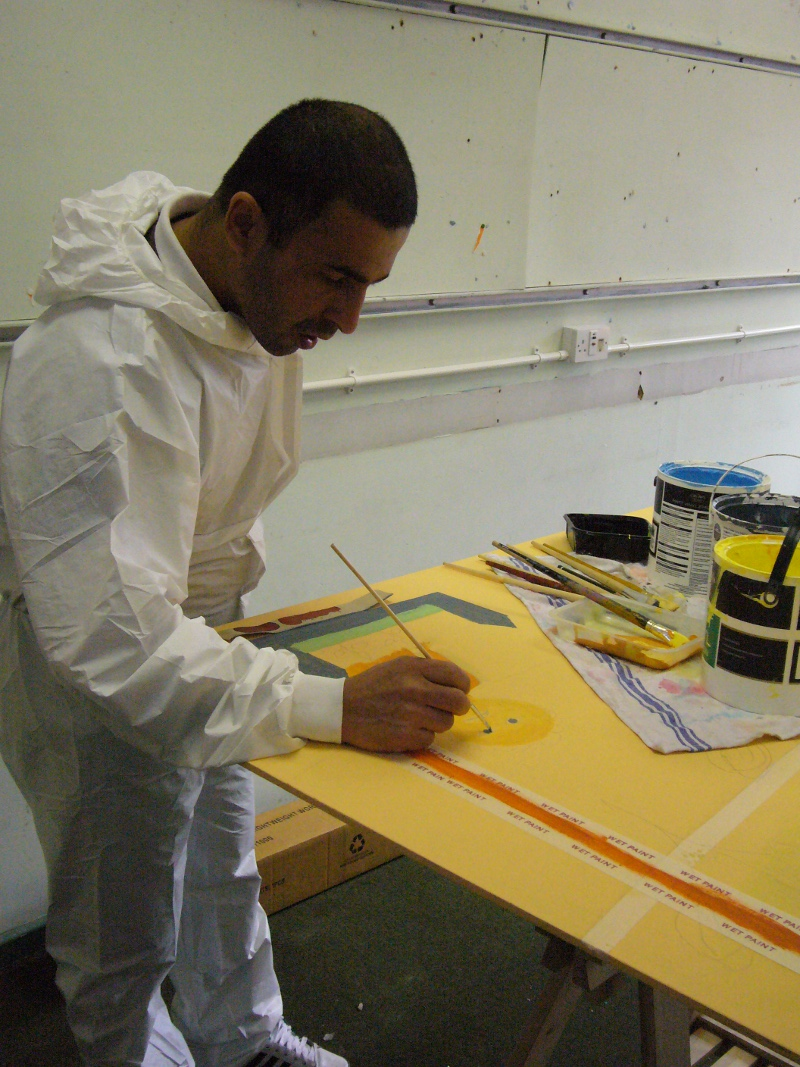 Ahmad is painting his mural design onto boards inside a room. He has short dark hair and is wearing a white jump-suit with the hood down.