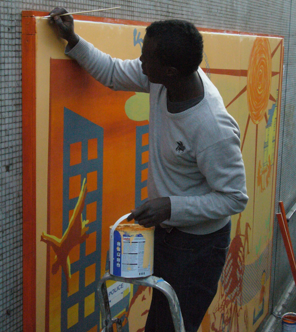 A man is painting the orange border of the mural now that it has been installed in the subway. He is standing on a step-ladder and is holding a paint can. He has short dark hair and is wearing a beige jumper.