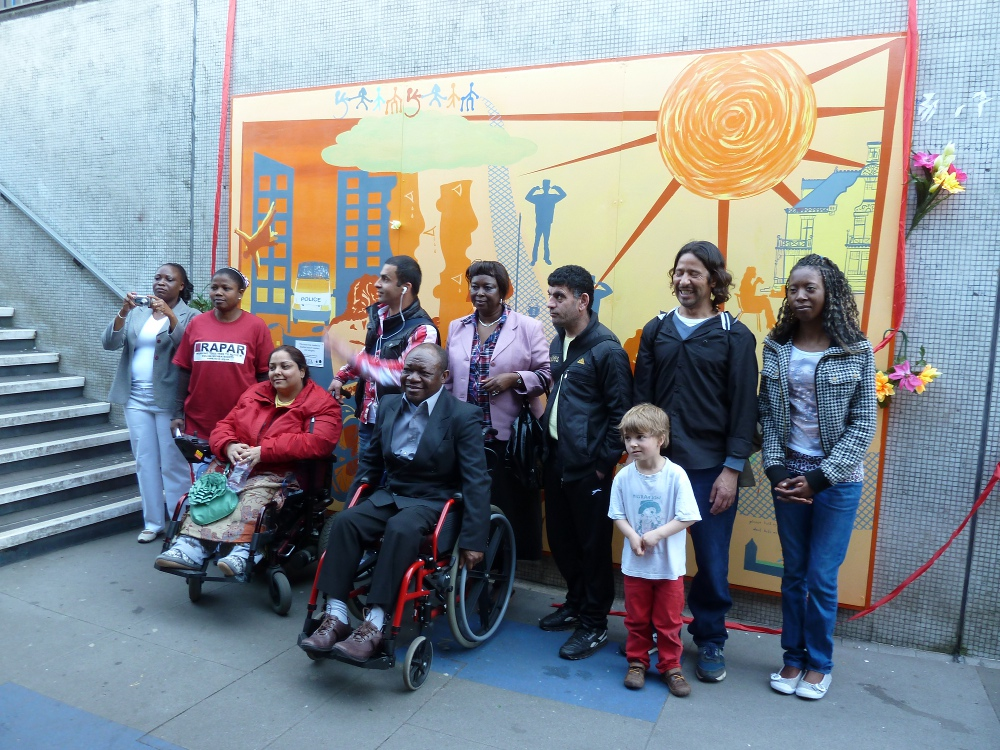 This picture shows all the participants standing in front of the mural. There are nine adults, five women and four men, and one little boy. Two of the participants, Manjeet and David, are wheelchair users.