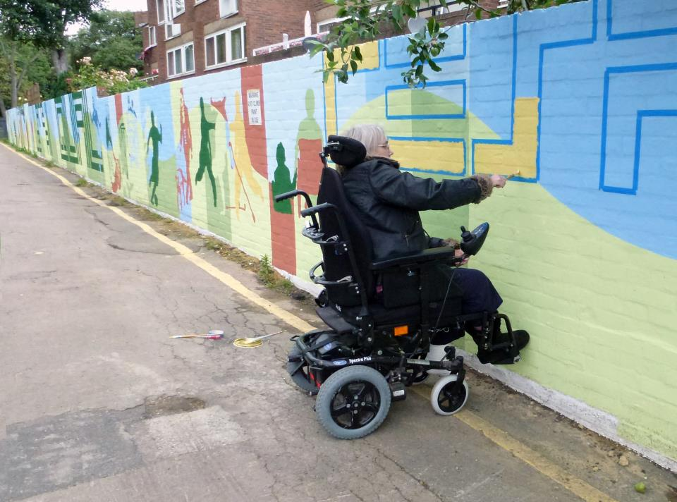 In this picture there is a woman with glasses and mid length grey hair painting the mural. The woman is a wheelchair user and is painting the letter S in yellow.