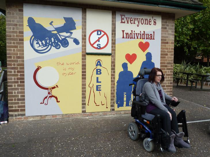 This photograph shows a woman sitting in a wheelchair in front of the painted mural. The mural is in three panels. On the right of the mural are the words 'Everyone's individual'. Below this are dark blue silhouettes of a wheelchair user holding hands with someone standing up. Red hearts are above their heads. The middle panel has the letters 'DIS' crossed out and beneath it the word 'ABLE' written vertically down the outline of a person using crutches. On the left there is a blue silhouette of a wheelchair user pushing a pram. Underneath this is a picture of a globe with the words 'The world is my oyster'.
