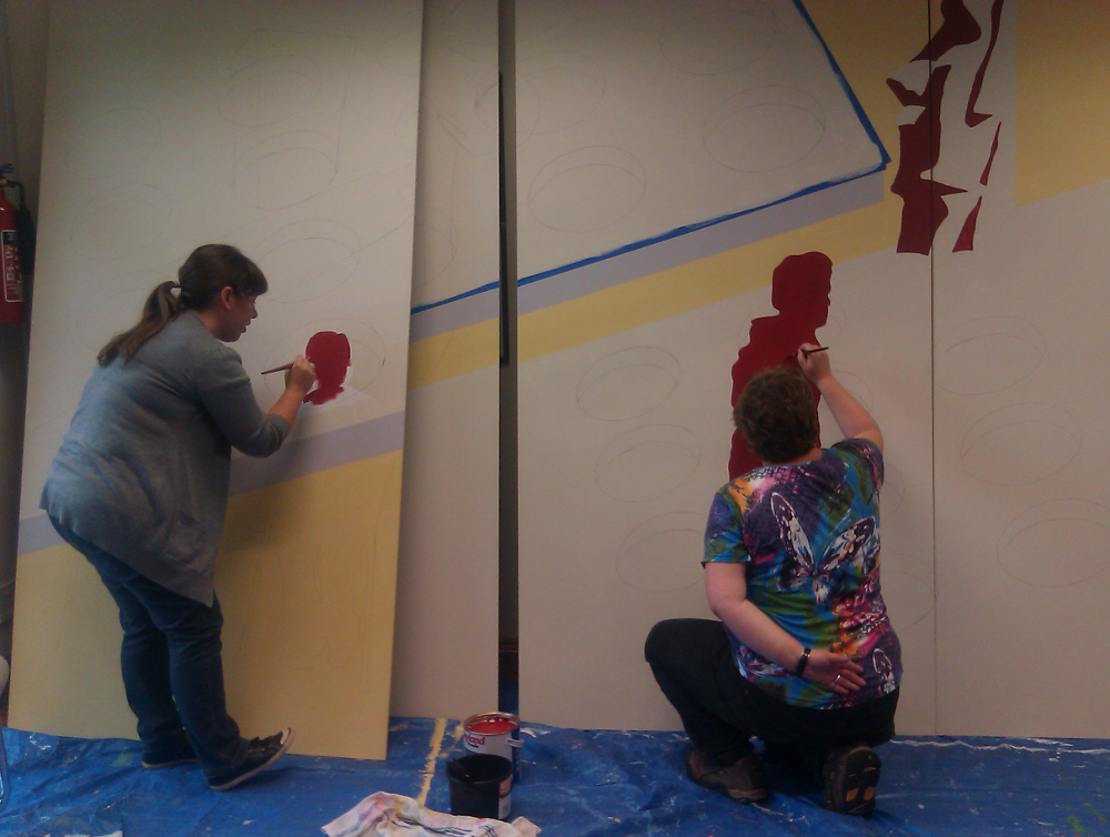This photo shows two women painting on boards that are propped against the wall. On the left there is  a woman with long dark hair tied in a single bunch. She is wearing a grey cardigan and blue jeans. Next to here there is another woman with one hand behind her back. She is wearing a brightly coloured t shirt and black trousers. She is kneeling on a blue tarpaulin on the ground. They are both painting with dark red shadows of figures against a background with cream, yellow and grey.