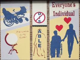 The mural is in three panels. On the right of the mural are the words \'Everyone\'s individual\'. Below this are dark blue silhouettes of a wheelchair user holding hands with someone standing up. Red hearts are above their heads. The middle panel has the letters \'DIS\' crossed out and beneath it the word \'ABLE\' written vertically down the outline of a person using crutches. On the left there is a blue silhouette of a wheelchair user pushing a pram. Underneath this is a picture of a globe with the words \'The world is my oyster\'.'